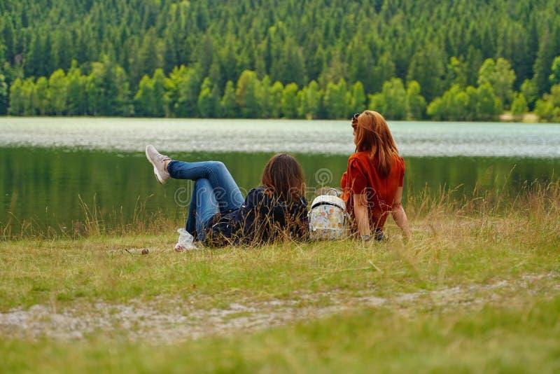 休息在湖附近的少女 免版税图库摄影