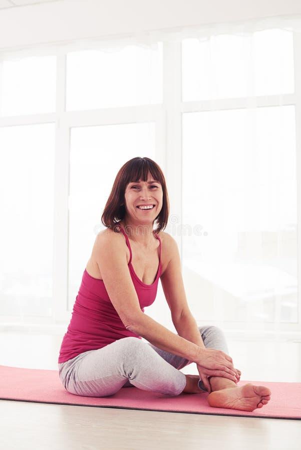 休息在瑜伽锻炼以后的微笑的迷人的妇女 库存图片