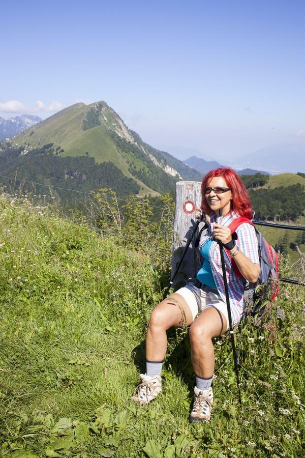 休息在电篱芭附近的愉快的妇女远足者 库存照片