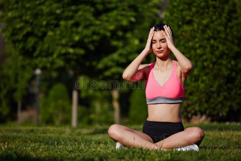 休息在美好的树背景的公园的明亮的运动服的可爱的运动的女孩 免版税库存图片
