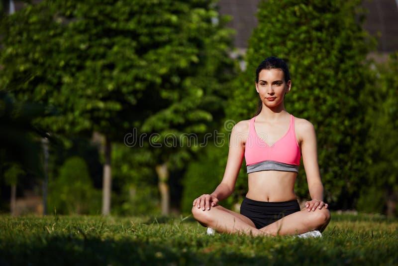 休息在美好的树背景的公园的明亮的运动服的年轻运动的女孩 库存图片
