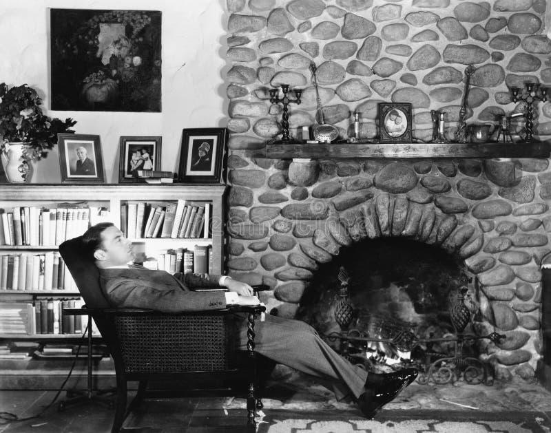 休息在胳膊椅子的一个年轻人的档案在壁炉附近(所有人被描述不更长生存,并且庄园不存在 免版税图库摄影