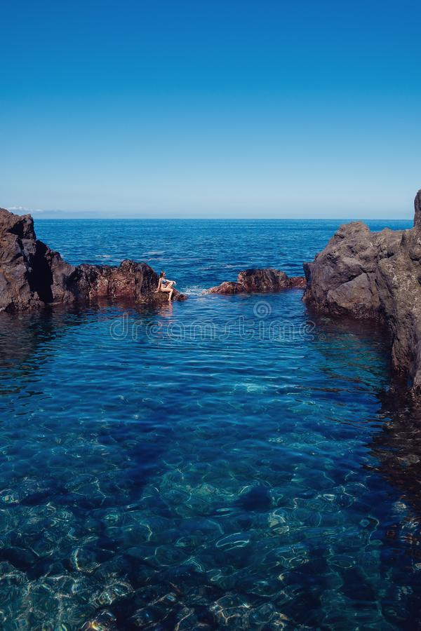 休息在自然海洋游泳池的美丽的女孩 库存图片