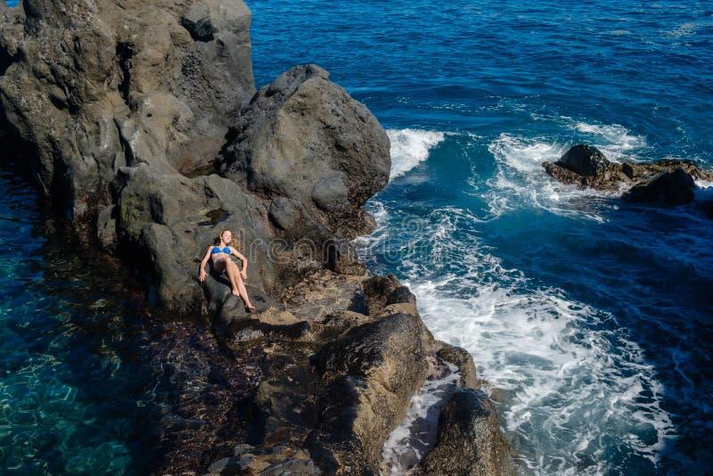休息在自然海洋游泳池的美丽的女孩 免版税库存照片