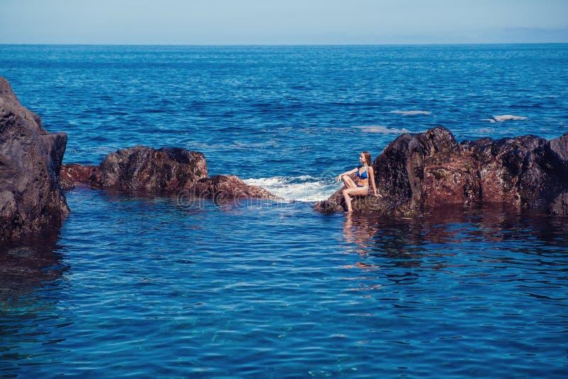 休息在自然海洋游泳池的美丽的女孩 免版税库存图片