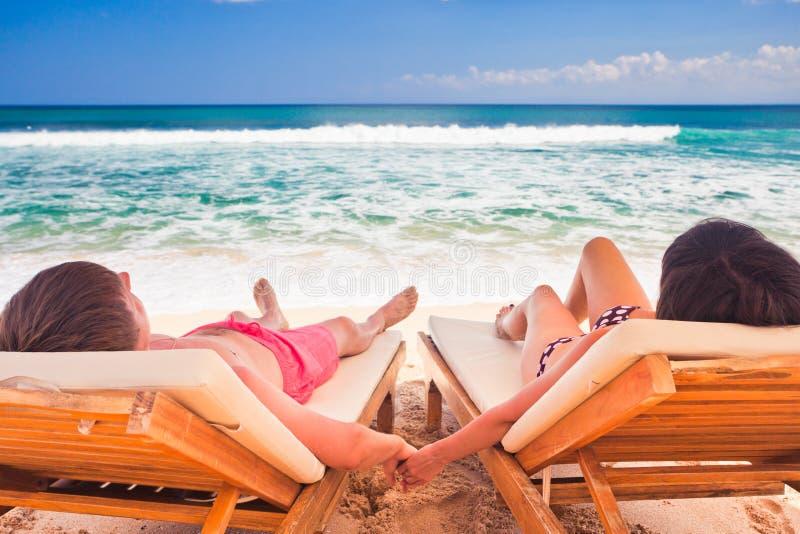 休息在蓝色海洋附近的婚礼夫妇 库存图片