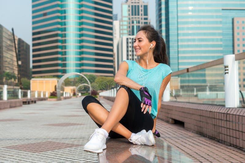 休息在行使以后,微笑的年轻健身妇女,坐对长凳在市中心 免版税库存照片