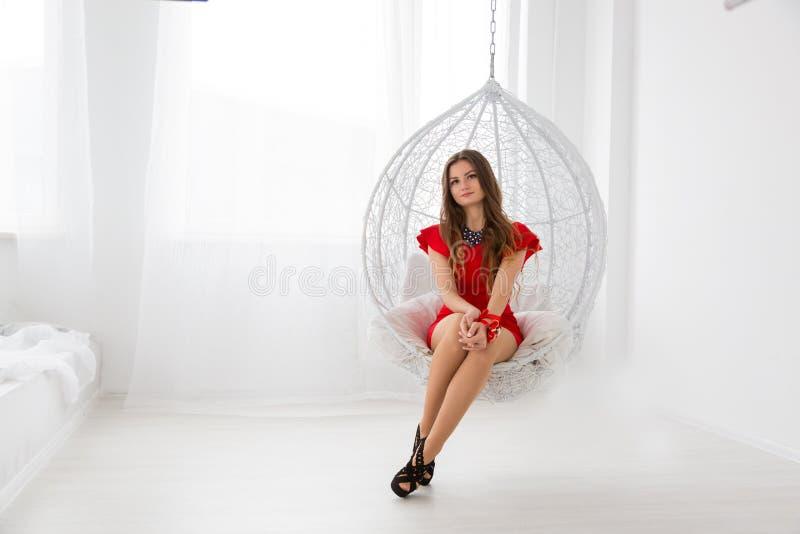 休息在象球形的装饰摇摆的红色礼服的年轻美丽的女孩 放松的典雅和舒适地方 免版税库存照片
