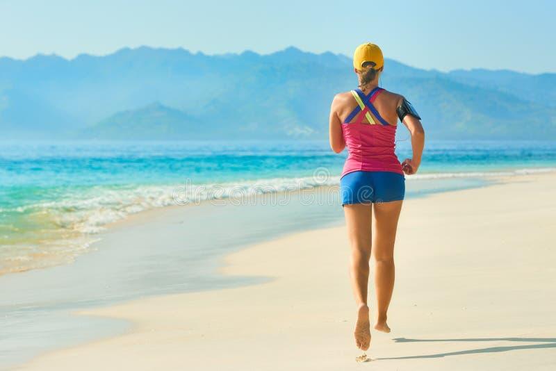 休息在跑步的训练以后的运动员赛跑者户外在海滩 库存照片
