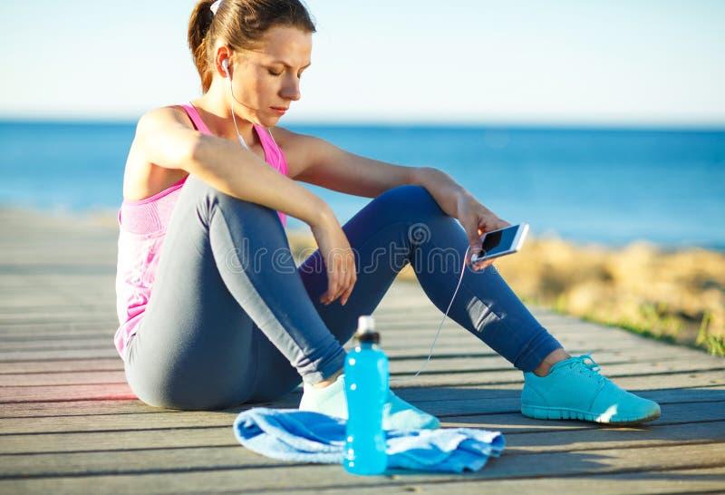 休息在跑的运动妇女在早晨训练以后  免版税库存图片