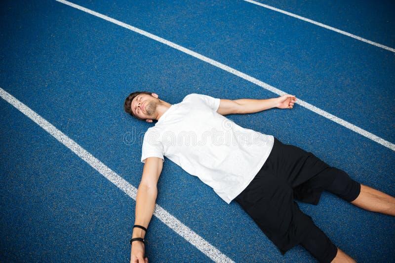 休息在跑以后的疲乏的男性运动员,当说谎在跑马场时 免版税库存照片