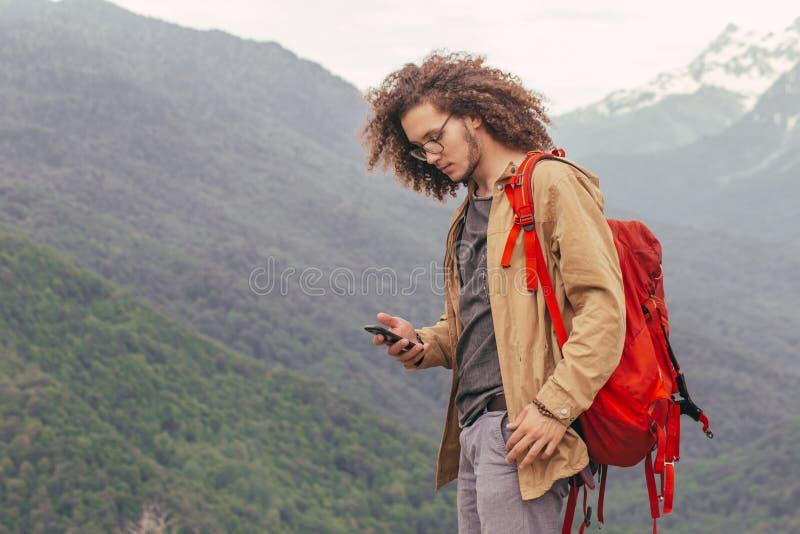 休息在远足的人坐和浏览他的电话的旅行期间 库存图片