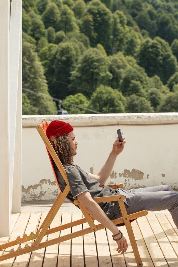 休息在远足的人旅行期间坐椅子浏览智能手机 免版税库存图片