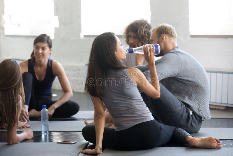 休息在锻炼以后的小组年轻运动的人民 免版税库存照片