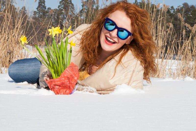 休息在雪的激动的令人敬佩的妇女水平的照片  免版税库存照片