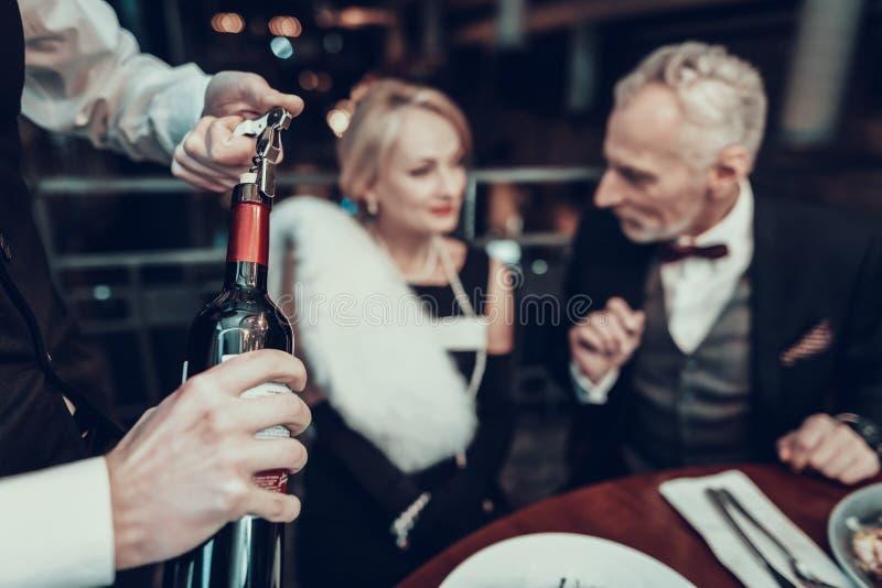 休息在餐馆和侍者开放酒的夫妇 免版税库存图片