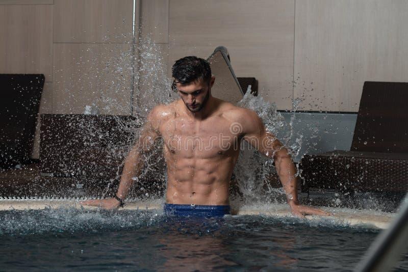 休息在水池的男性游泳者 库存照片