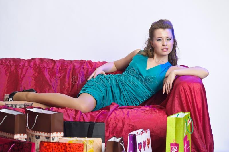 休息在购物以后的愉快和疲乏的妇女 库存图片
