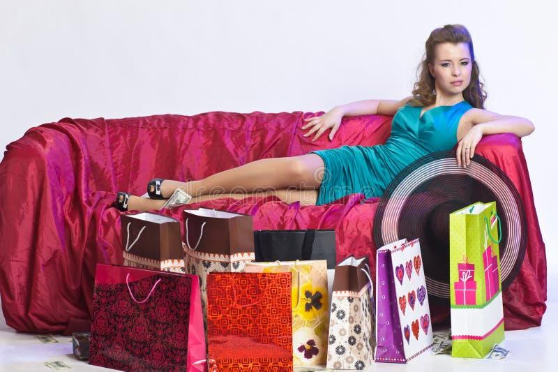 休息在购物以后的愉快和疲乏的妇女 免版税库存图片