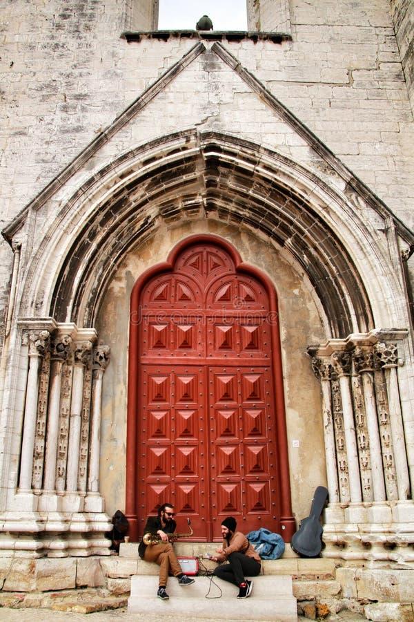 休息在Convento的门的音乐家在里斯本做卡尔穆 免版税库存图片