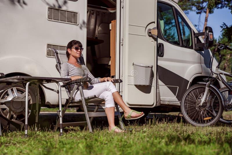休息在motorhomes附近的妇女本质上 家庭度假旅行, 库存照片