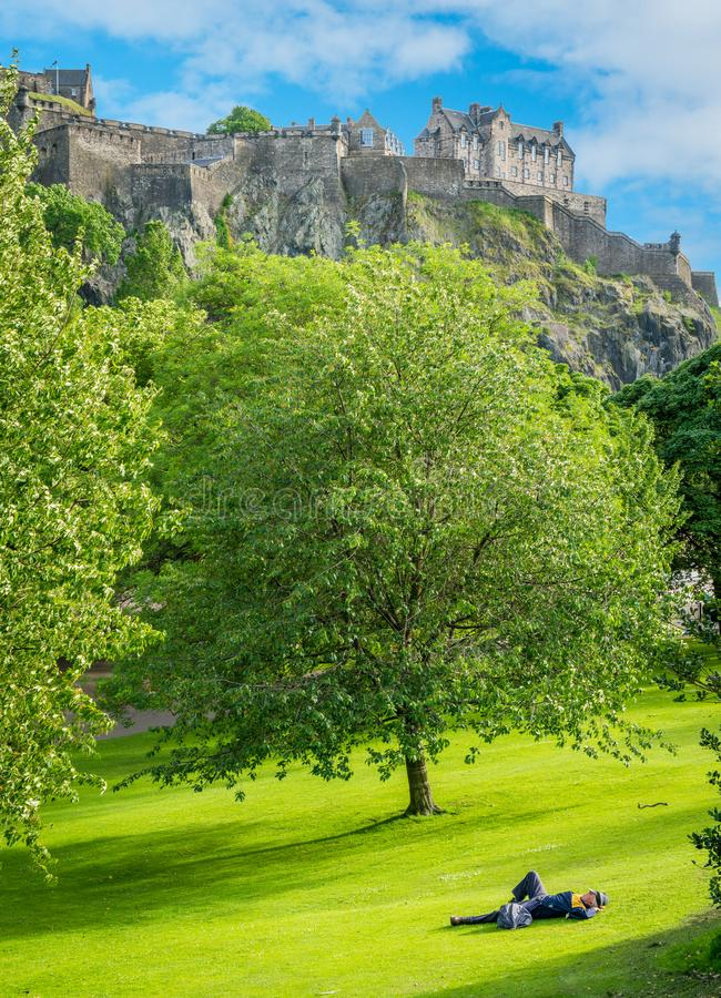 休息在Street Gardens王子的有爱丁堡城堡的一个人在背景中 苏格兰 免版税库存照片