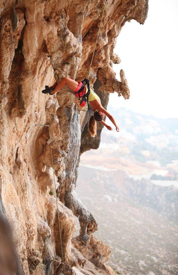 休息女性的攀岩运动员,当垂悬在绳索时 库存图片