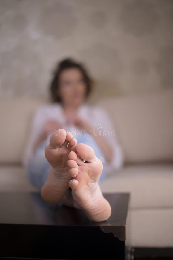 休息她的在胸口的妇女赤裸脚 库存图片