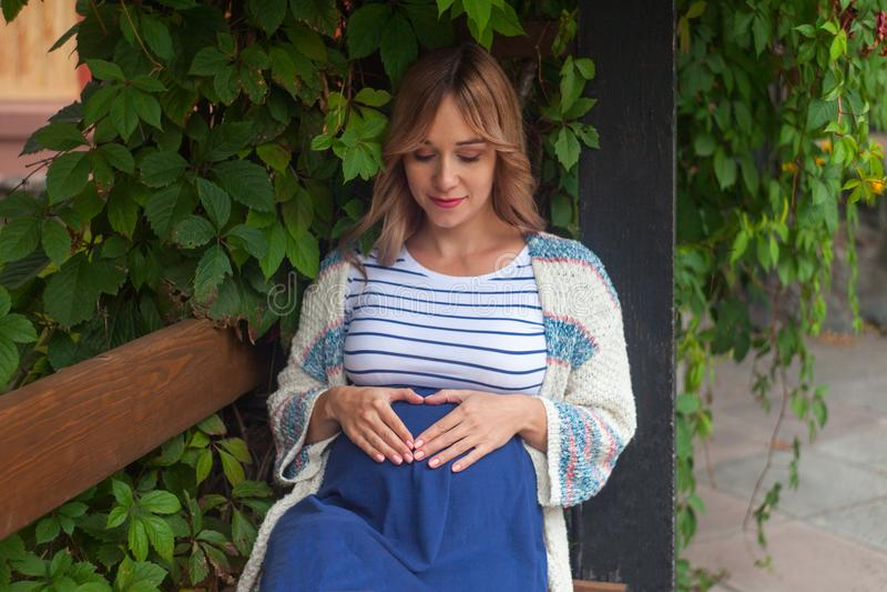 休息室外,愉快的怀孕概念的孕妇画象 免版税库存照片