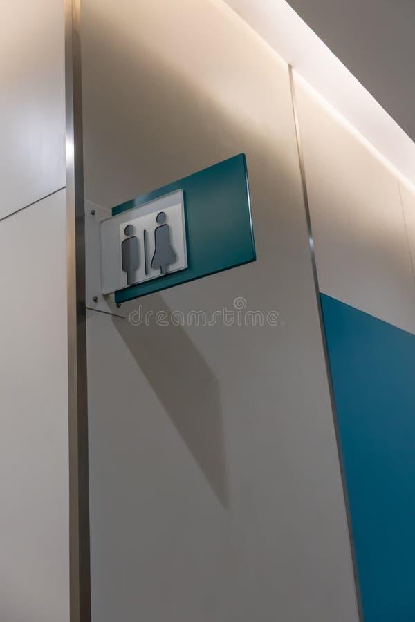 休息室标志或洗手间标志与男人和妇女象集合符号在白色混凝土墙背景 图库摄影