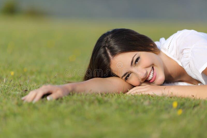 休息愉快的妇女微笑和放松在草 免版税图库摄影