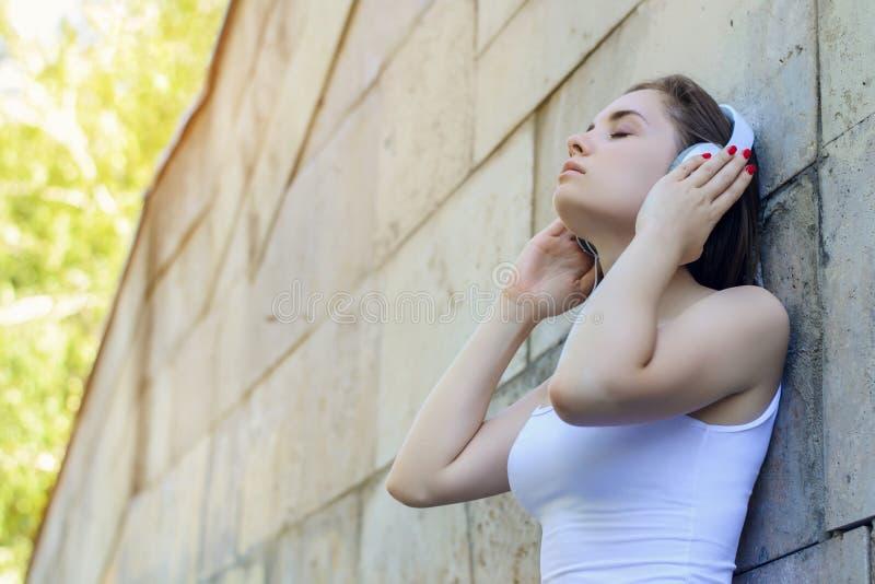 休息放松使停留断裂爱好生活方式变冷享受乐趣喜悦梦想梦想的闭合的眼睛概念 耳机的年轻美丽的女孩 库存图片