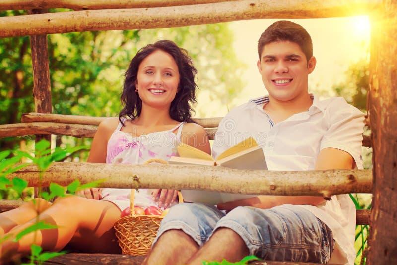 休息用苹果和书instagram窗框的年轻夫妇 免版税库存照片