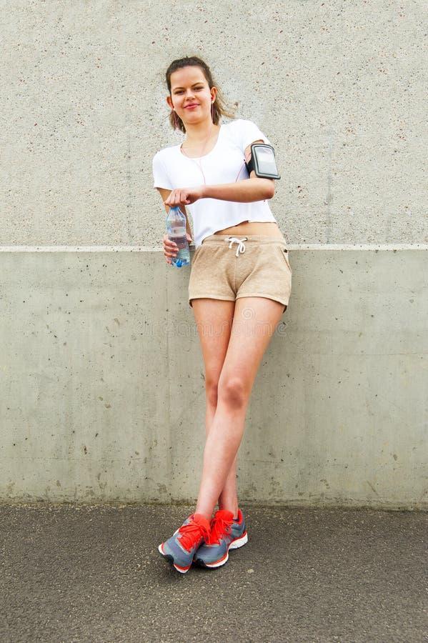 休息由墙壁的女孩 Joging成套装备 大微笑 免版税库存照片