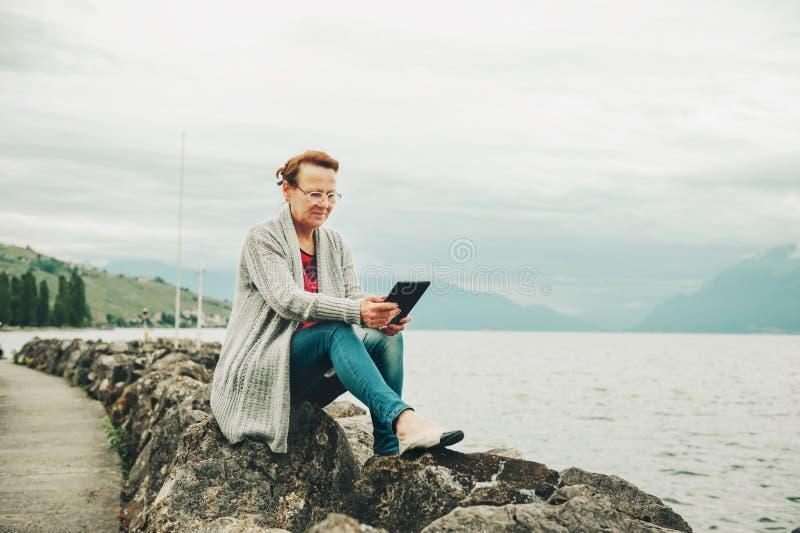 休息由湖的中年妇女 库存图片