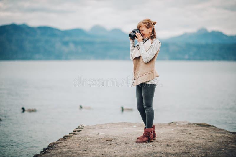 休息由湖的相当小女孩室外画象  免版税库存图片