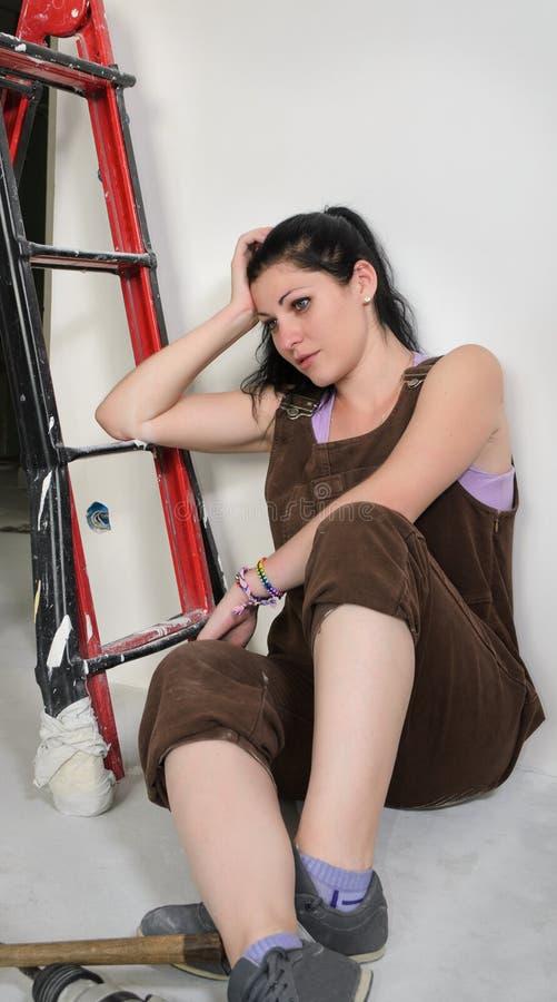 休息疲乏的妇女,当重新装修时 库存照片