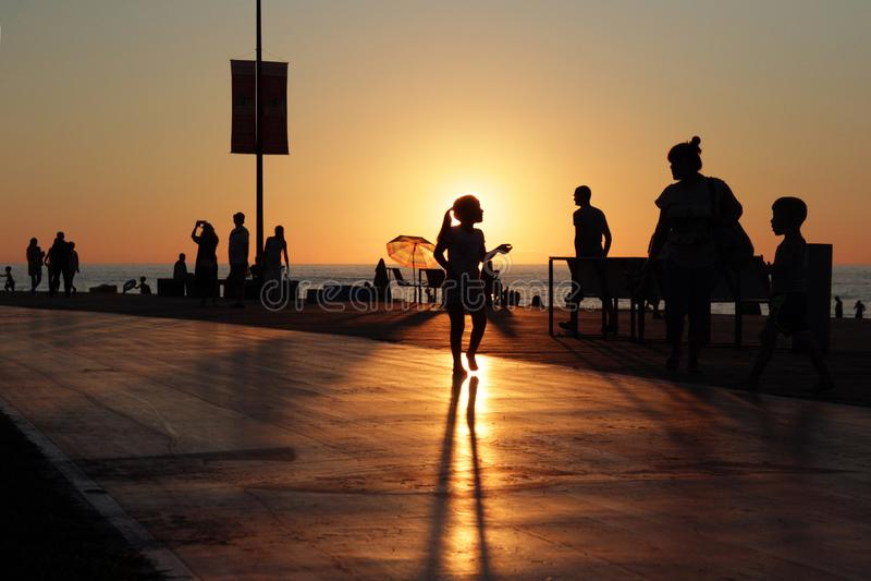 休息的人剪影海海滩crowdy日落背景的 免版税库存照片