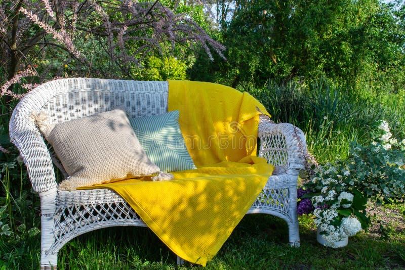 休息的可爱的地方在绿色庭院-有卵黄质黄色毯子和两个不同坐垫的白色柳条长沙发里 库存照片