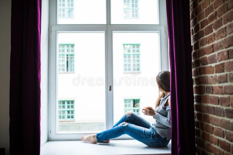 休息的和想法的妇女 有在家和喝坐窗台的茶的镇静女孩或咖啡 免版税库存照片