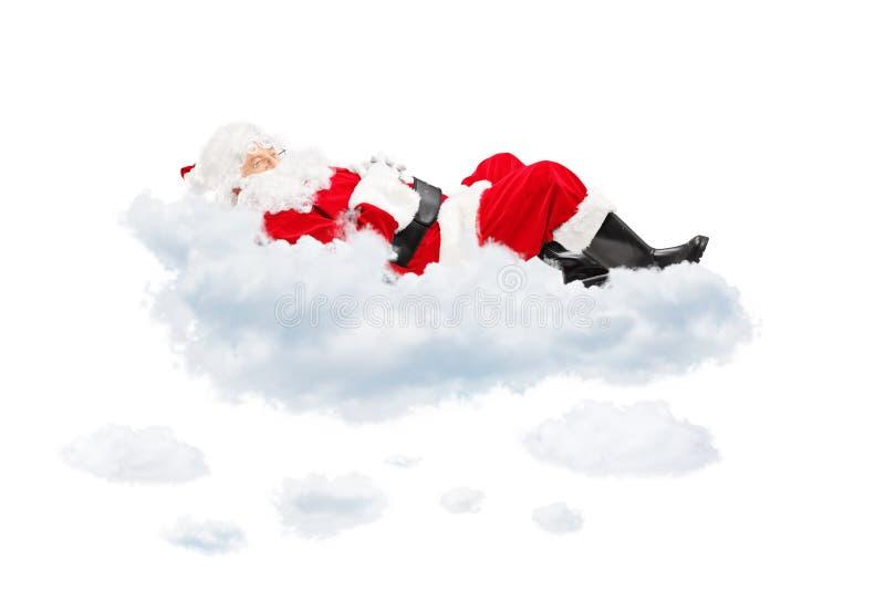 休息的圣诞老人,当说谎在云彩时 库存图片
