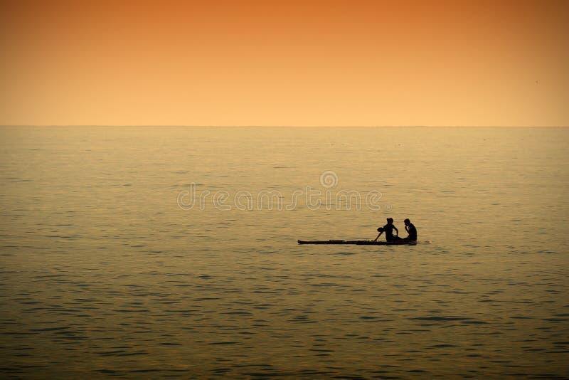 休息的夫妇,当paddleboarding在风平浪静在日落时间时 库存图片