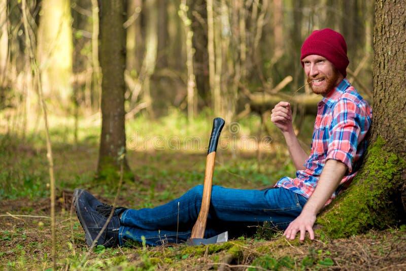 休息的愉快的伐木工人在树附近 库存图片