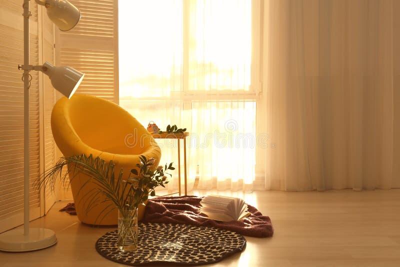 休息的舒适地方与扶手椅子和软的格子花呢披肩在窗口附近在屋子里 免版税库存照片