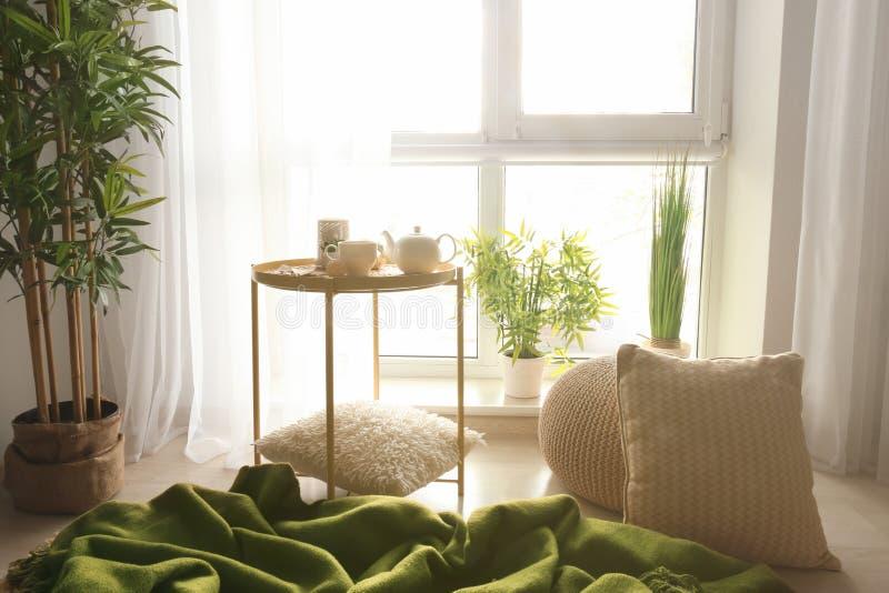 休息的舒适地方与枕头和软的格子花呢披肩在窗口附近在屋子里 图库摄影
