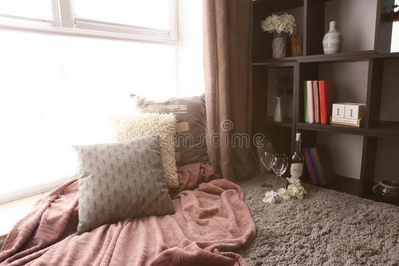 休息的舒适地方与枕头和软的格子花呢披肩在窗口附近在屋子里 免版税库存照片