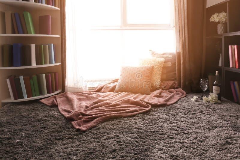 休息的舒适地方与枕头和软的格子花呢披肩在窗口附近在屋子里 免版税库存图片