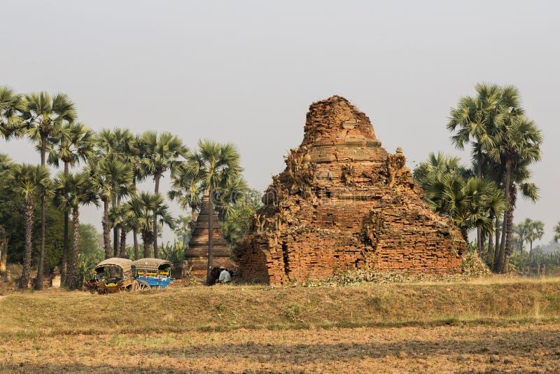 休息缅甸人和两个典型的五颜六色的推车的砖寺庙废墟 图库摄影