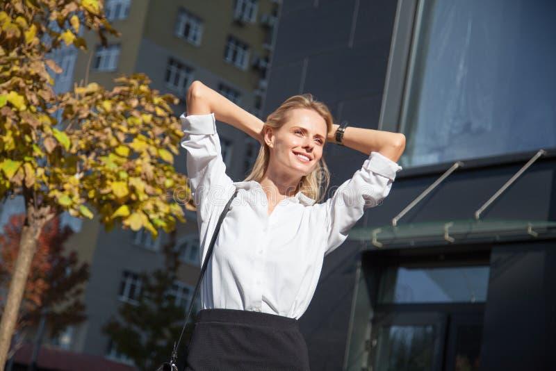 休息轻松的镇静愉快的妇女握在头后的健康休假手呼吸新鲜空气反对办公室 免版税库存照片