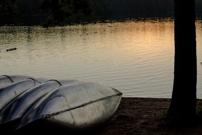 休息靠近海的四个金属独木舟在日落 库存照片